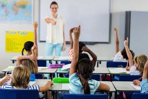 Teacher pointing students with raised hands to highlight engagement and interaction.