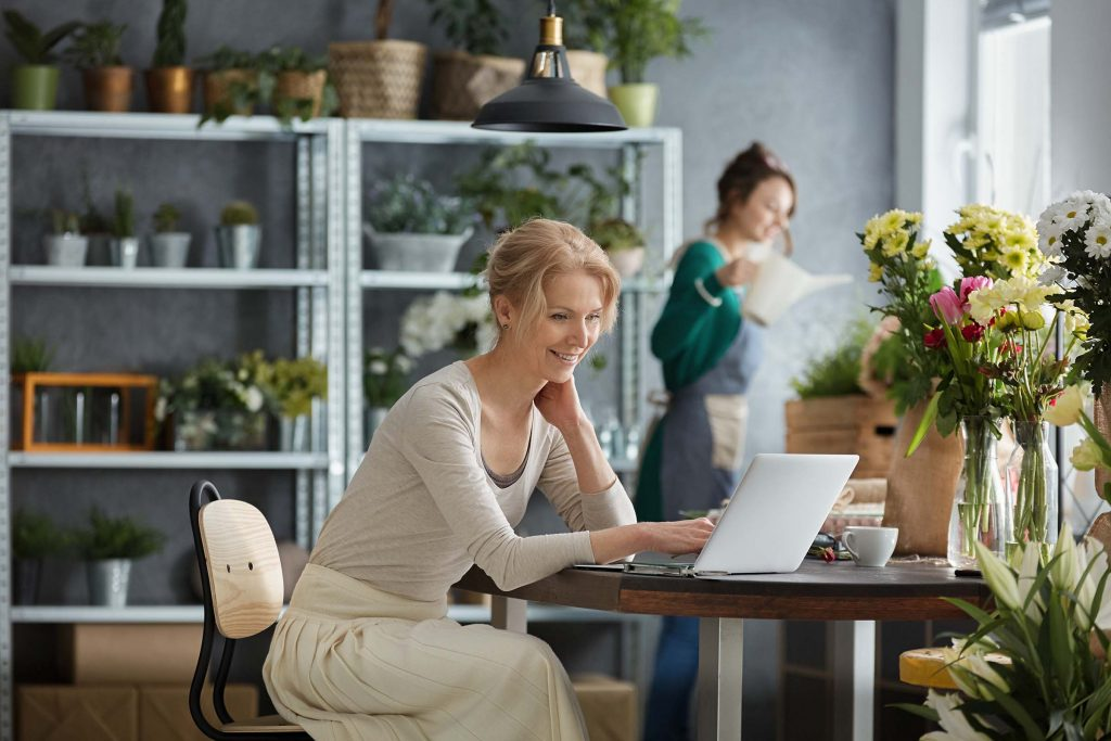 Two smiling florists working in a flower shop while one is at a laptop sending an email newsletter.