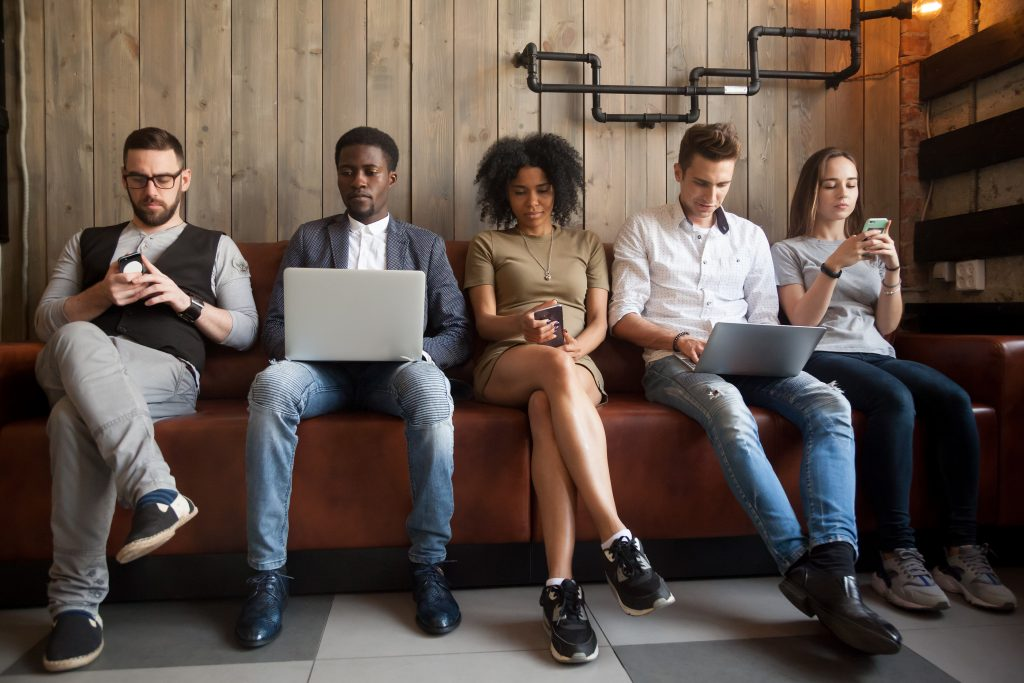 Diverse young people sitting in row on couch together working on various electronic devices.
