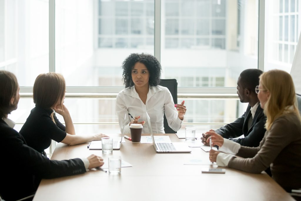 A woman meeting with her colleagues for an upper-level management meeting