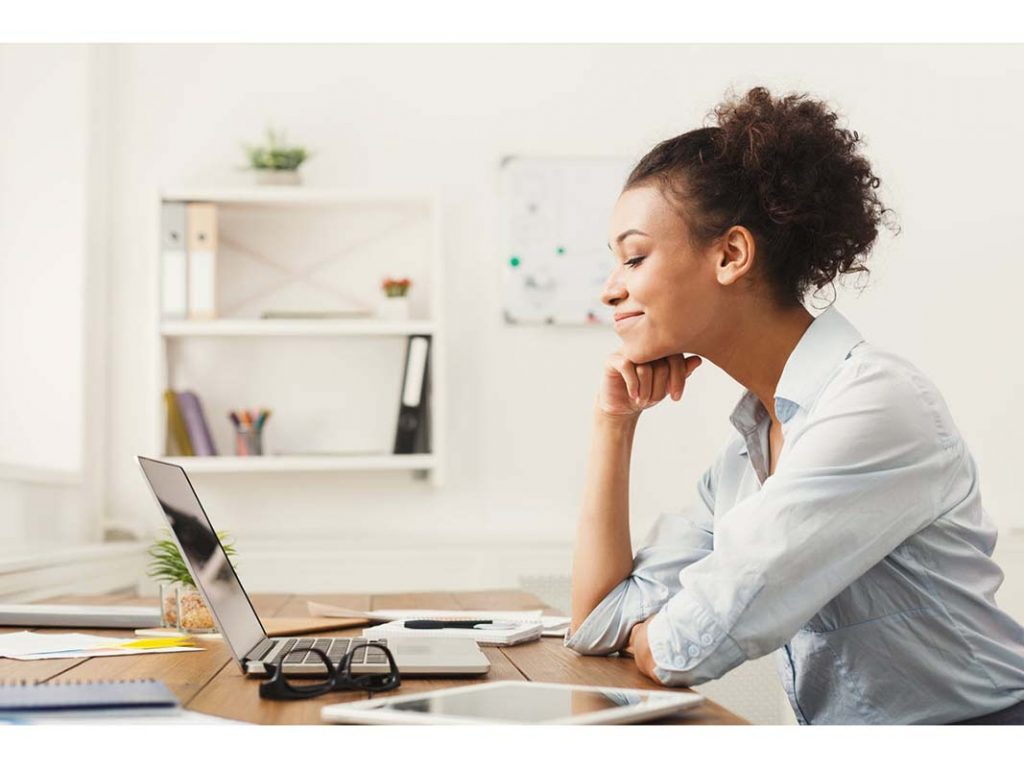 Image of a happy woman satisfied after sending out an email campaign.
