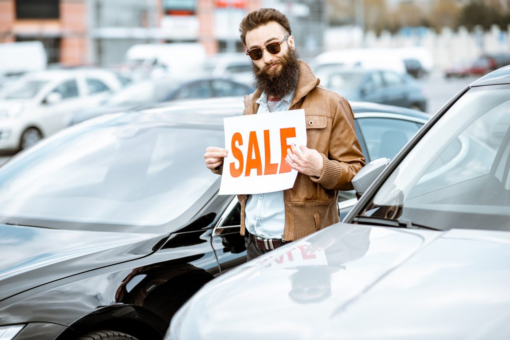 Questionable car salesman sneaking up between cars with a SALE sign.