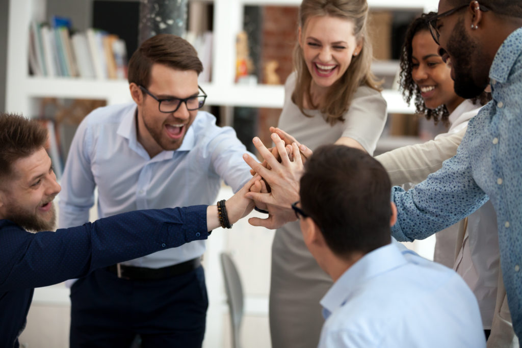 Excited motivated diverse team people give high five in office