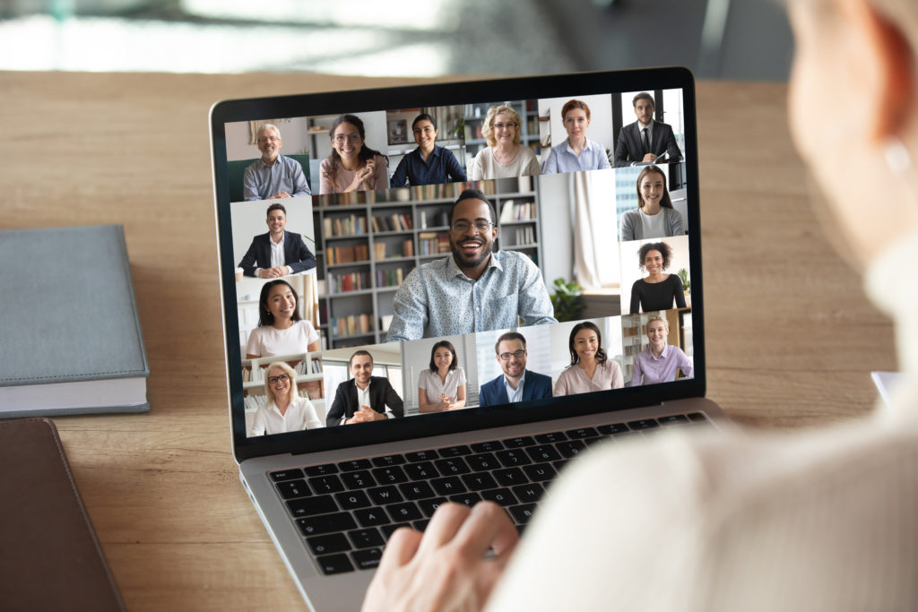 A laptop showing a video call full of coworkers.