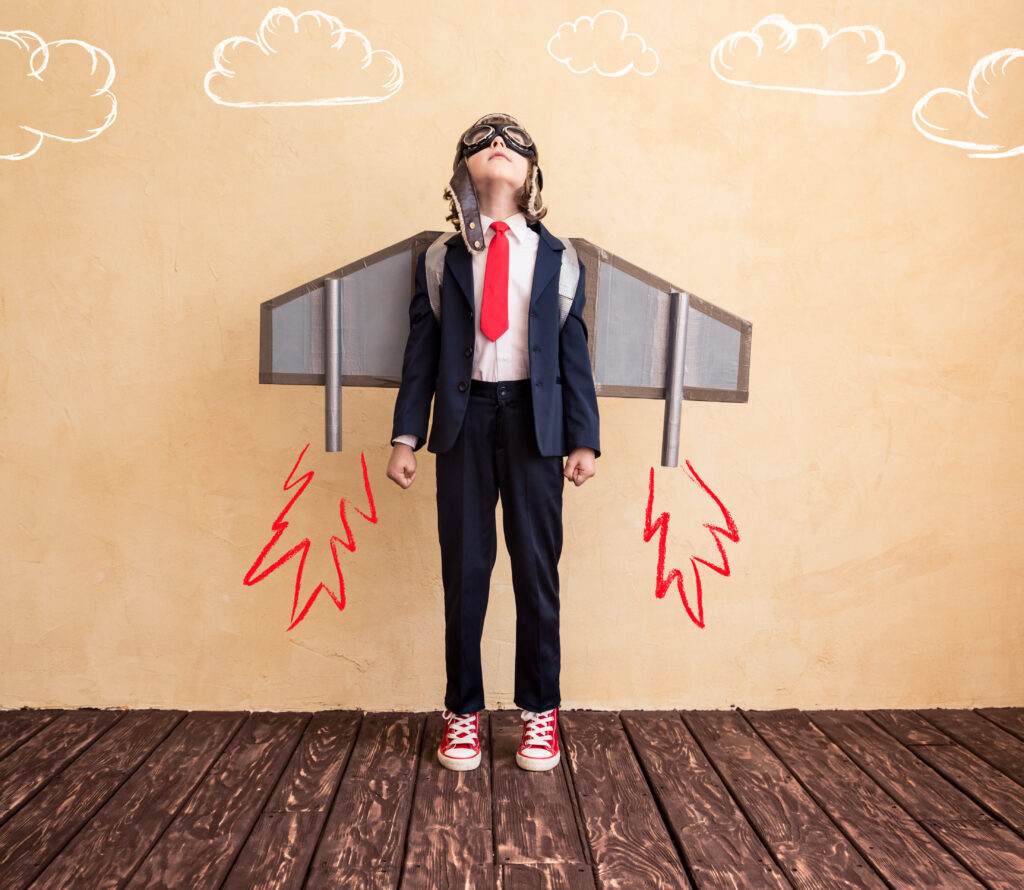 A young child dressed with toy paper wings in a business suit, ready to launch his career.