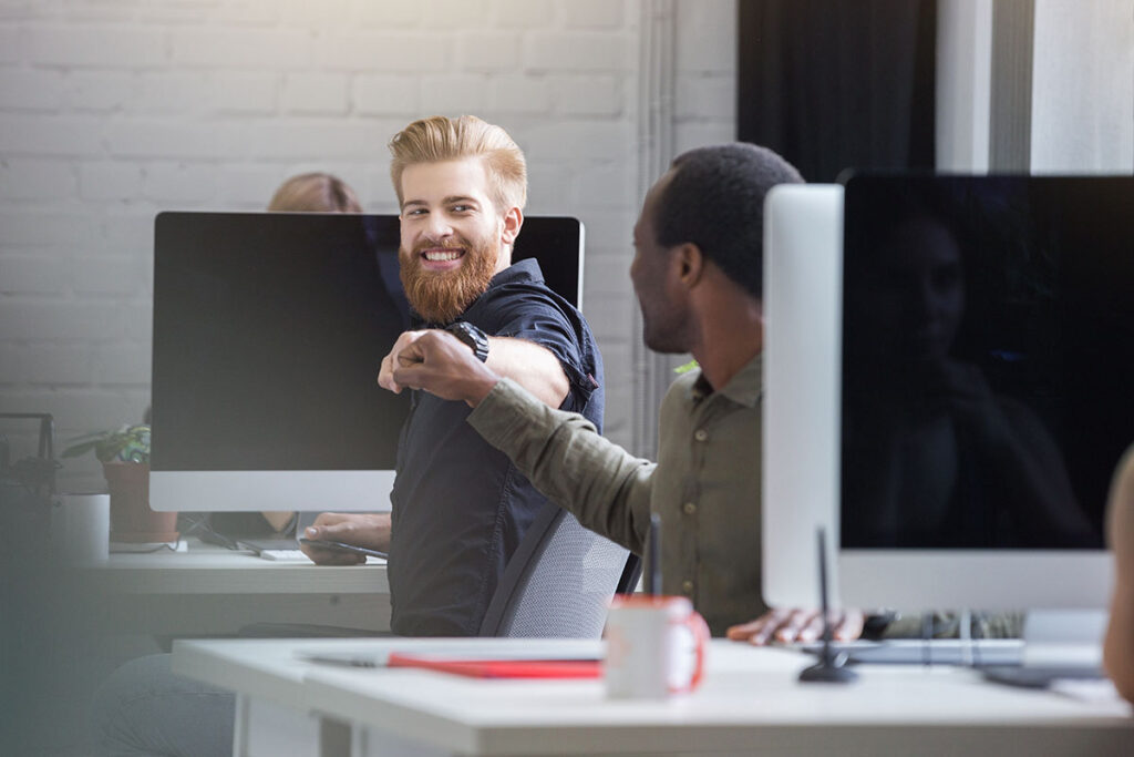 Co-workers share a fist bump in an open office environment