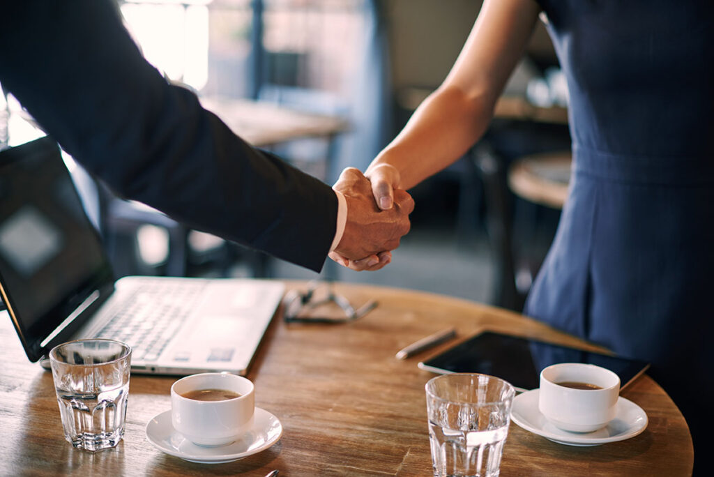 Two people shaking hands over a table with a laptop and empty glassware
